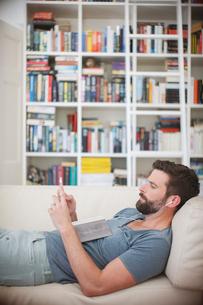 Man listening to music on sofaの写真素材 [FYI02161267]