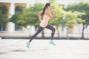 Woman running through city streetsの写真素材 [FYI02161285]