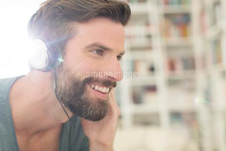 Man listening to music in living roomの写真素材 [FYI02161289]