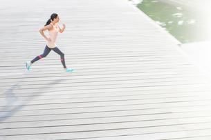 Woman running through city streetsの写真素材 [FYI02161291]