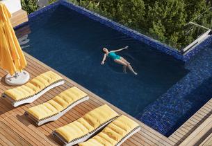 Woman floating in luxury swimming poolの写真素材 [FYI02161339]