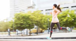 Woman running through city streetsの写真素材 [FYI02161381]