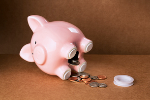 Piggy bank spilling out change onto counterの写真素材 [FYI02161385]