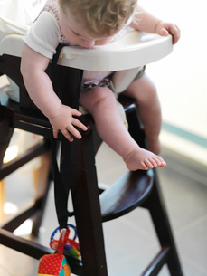 Baby girl in high chair reaching for toyの写真素材 [FYI02161459]