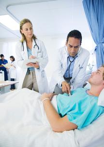 Doctors examining patient in hospital roomの写真素材 [FYI02161465]