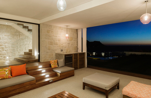 Luxury living room overlooking ocean at nightの写真素材 [FYI02161495]