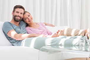 Couple relaxing together on sofa in modern living roomの写真素材 [FYI02161606]