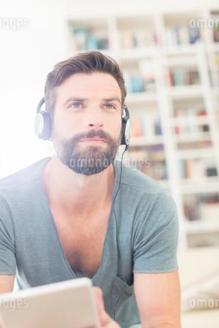 Man listening to music in living roomの写真素材 [FYI02161612]