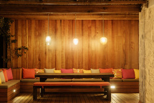 Pendant lights illuminated over patio bench with cushionsの写真素材 [FYI02161624]
