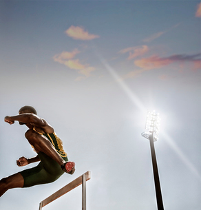 Track and field athlete clearing hurdleの写真素材 [FYI02161645]