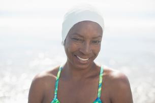 Portrait of smiling woman in swimming cap at beachの写真素材 [FYI02161661]