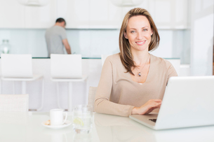 Woman using laptop at breakfast tableの写真素材 [FYI02161671]