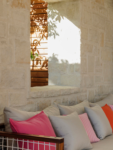 Stone wall  behind patio bench with cushionsの写真素材 [FYI02161678]