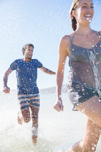 Couple splashing in water on beachの写真素材 [FYI02161700]