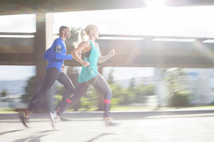 Couple running through city streets togetherの写真素材 [FYI02161736]