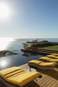 Sun shining over lounge chairs at poolside overlooking oceanの写真素材 [FYI02161793]