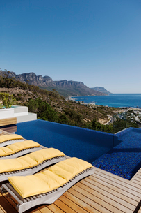 Lounge chairs at poolside overlooking oceanの写真素材 [FYI02161805]