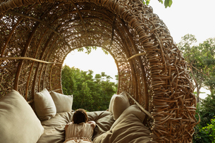Woman laying in nest tree houseの写真素材 [FYI02161842]