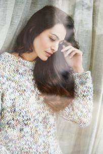 Woman standing by windowの写真素材 [FYI02161856]