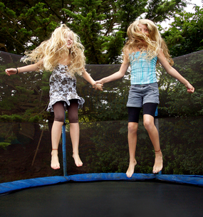 Girls jumping on trampoline outdoorsの写真素材 [FYI02161922]