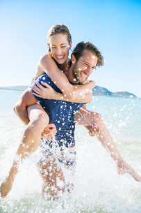 Woman riding piggy back on boyfriend in waterの写真素材 [FYI02161963]