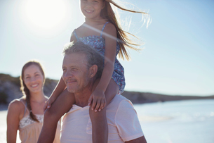 Father holding daughter on shoulders on beachの写真素材 [FYI02161975]