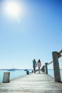 Couple holding hands walking along wooden dockの写真素材 [FYI02162027]