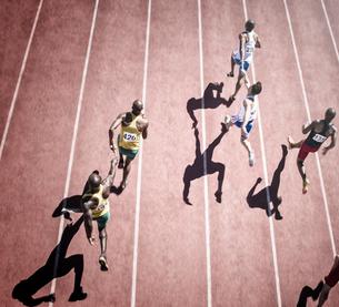 Relay runners handing off baton on trackの写真素材 [FYI02162092]