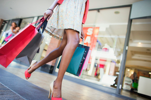 Low angle view of woman carrying shopping bags in shopping mallの写真素材 [FYI02162206]