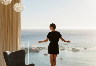 Woman standing at balcony railing overlooking oceanの写真素材 [FYI02162295]