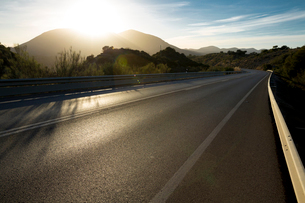 Sun shining over mountains and open roadの写真素材 [FYI02162362]