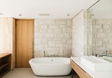 Stone walls behind soaking tub in modern bathroomの写真素材 [FYI02162398]