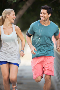 Couple running through city streets togetherの写真素材 [FYI02162429]