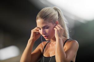 Woman exercising and listening to headphonesの写真素材 [FYI02162440]