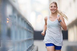 Woman running through city streetsの写真素材 [FYI02162531]