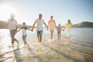 Family walking in shallow water on beachの写真素材 [FYI02162552]