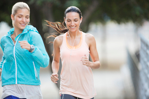 Women running through city streets togetherの写真素材 [FYI02162606]