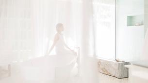 Woman in modern bathroom viewed through sheer curtainの写真素材 [FYI02162641]