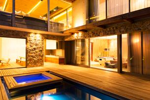 Modern house overlooking illuminated swimming pool at nightの写真素材 [FYI02162671]
