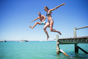 Couple jumping off wooden dock into waterの写真素材 [FYI02162673]