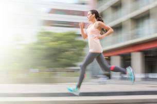 Woman running through city streetsの写真素材 [FYI02162684]