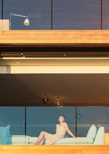 Woman sitting on sunny luxury balconyの写真素材 [FYI02162737]