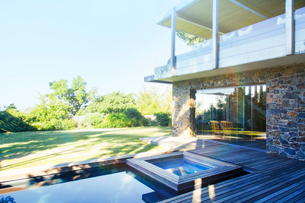 Modern house overlooking pool and wooden deckの写真素材 [FYI02162844]