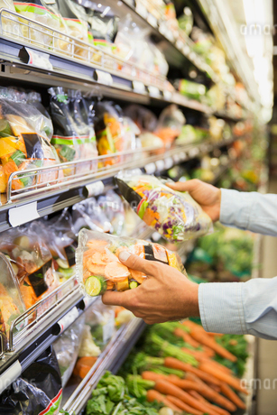 Close up of man comparing produce in grocery storeの写真素材 [FYI02162874]
