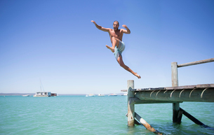 Couple jumping off wooden dock into waterの写真素材 [FYI02162902]
