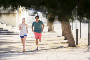 Couple running through city streets togetherの写真素材 [FYI02162904]