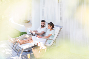 Couple relaxing together in lawn chairs outdoorsの写真素材 [FYI02162947]