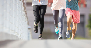 Friends running through city streetsの写真素材 [FYI02162970]
