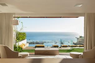 Sunny bedroom and patio overlooking oceanの写真素材 [FYI02162975]
