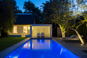 Lawn chairs on wooden deck by illuminated swimming pool at nightの写真素材 [FYI02162981]